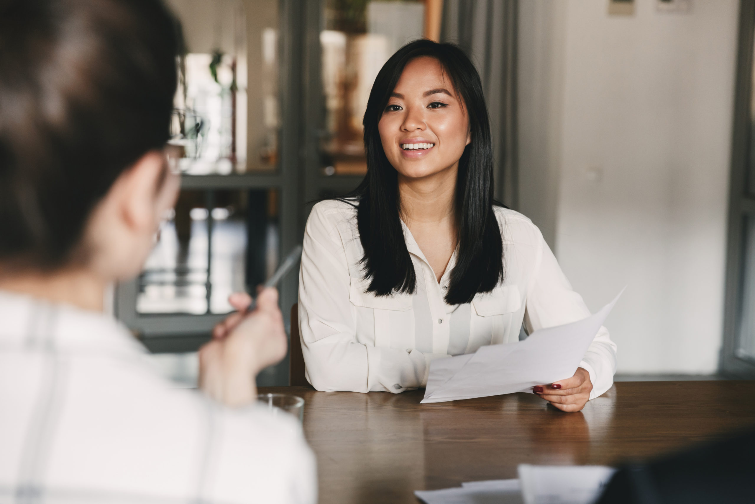 Business, career and placement concept - joyful asian woman smiling and holding resume while sitting in front of directors during corporate meeting or job interview